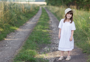 Photo sur Plexiglas Doux monstres Happy little girl in a hat and white dress stands on a road near field of rye.
