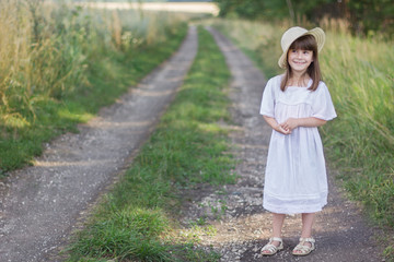 Photo sur Plexiglas Doux monstres Happy little girl on the road. Cute girl in a white dress stands near a field with spikelets of wheat.