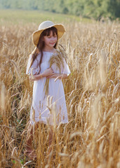 Photo sur Plexiglas Doux monstres Beautiful girl in a hat stands on a field of rye at sunset
