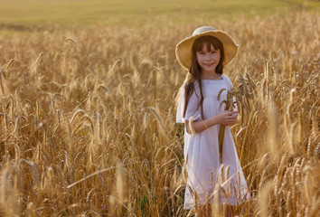 Photo sur Plexiglas Doux monstres Cute girl in a white dress on a field with spikelets of wheat