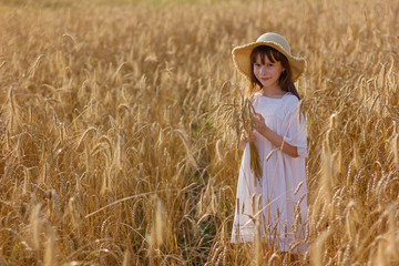 Photo sur Plexiglas Doux monstres Happy girl in a hat stands in a field of ripe rye in the sunset light.