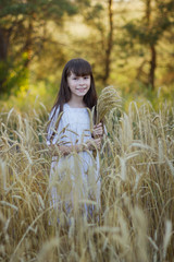 Photo sur Plexiglas Doux monstres Cute girl in a white dress with spikelets of wheat stands in a field of ripe rye in the sunset light.