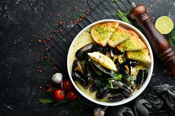Boiled mussels in cream sauce and garlic. Top view. Free space for text.