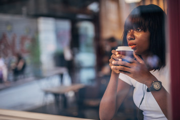 Papiers peints Cafe Modern black woman drinking coffee in cafe