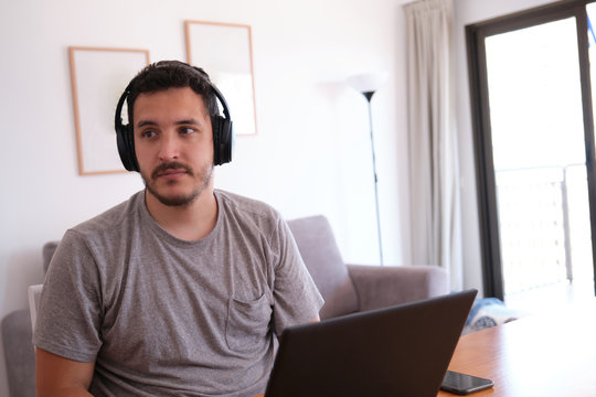 Young man wearing headphones distracted watching series, videos, instead his online classes. Studying online and e-learning concept.