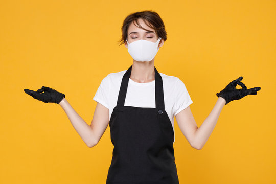 Young woman 20s barista bartender barman employee in apron sterile face mask to safe from coronavirus virus covid-19 2019-ncov during quarantine hold hands yoga gesture isolated on yellow background.