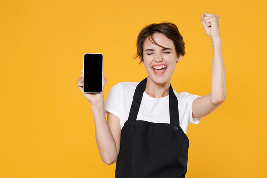 Happy young female woman 20s barista bartender barman employee in apron hold mobile phone with blank empty screen mock up copy space doing winner gesture isolated on yellow background studio portrait.
