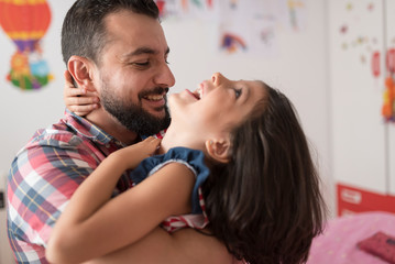 Father hugs and plays with his daughter in the bedroom of their home