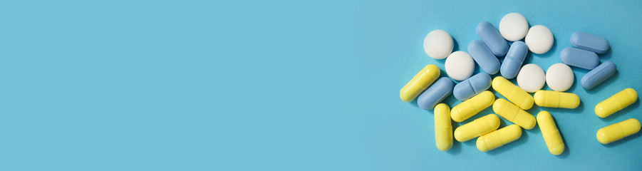 pills on a blue background, multicolored pills. with place for text from the left. banner
