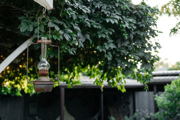 Vintage vintage lantern hangs on the porch of a private house on a background of greenery in the evening.