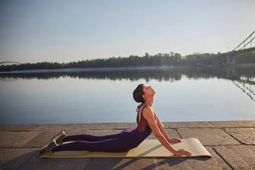 Beautiful female practicing yoga Cobra Pose outdoor