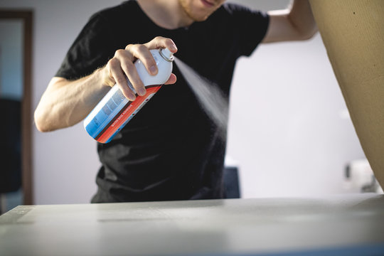 Selective focus of artisan using adhesive spray while working on screen printing machine