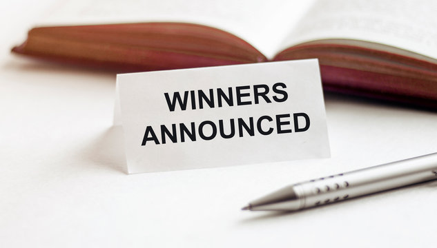 piece of paper with text Winners Announced on the background of books, pens, on a white background