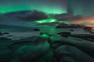 Photo sur Plexiglas Aurore polaire Northern lights (Aurora Borealis) over the starry night sky. Uttakleiv beach in Lofoten, Norway