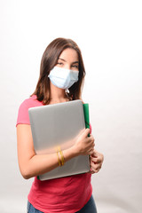 portrait of beautiful young girl student isolated on white background wearing a covid 19 surgical mask protection