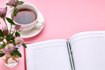 above view for pink desk with red diary of notepad and tea cup on it. table decorated with flowers. office workplace background backdrop