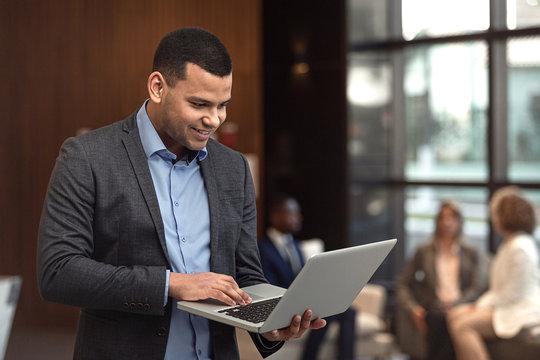 Executivo latino trabalhando em computador portátil.
