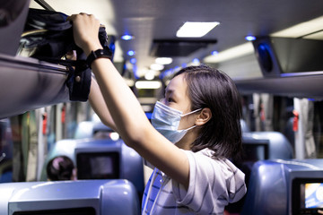 Asian female student stowed her backpack in a overhead storage on the school bus,child girl wearing protective mask to safety from the Coronavirus,field trip in new normal conditions under COVID-19