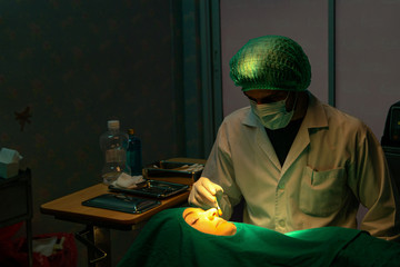 Concentrated Surgical operating a patient in an operation theater. the doctor 'll operate to face or nose of  the patient throughout the surgery.