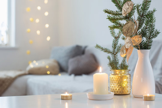 Christmas decorations with burning candles in white interior
