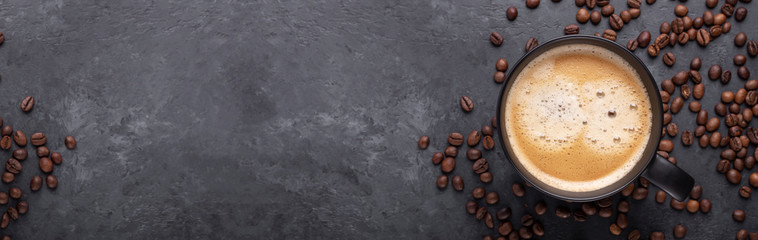 Horizontal banner with cup of coffee and coffee beans on dark stone background. Top view. Copy space