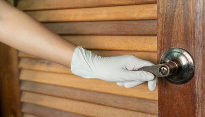 Women wear a glove and catch at a door handle.