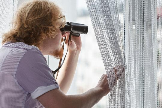Man with binoculars spying on neighbors