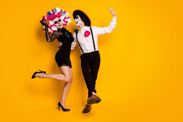 Full length photo of pretty couple man lady dance latin carnival wear black mini short dress high heels death costume roses headband sombrero suspenders isolated yellow color background