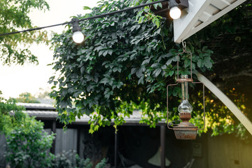 Antique vintage iron lantern hangs on the terrace of the house against the backdrop of greenery in the evening.