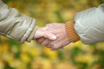 Elderly couple holding hands in autumn park