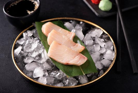 yellowtail sashimi on ice in a black plate
