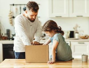 Father and kid unpacking carton box at home.