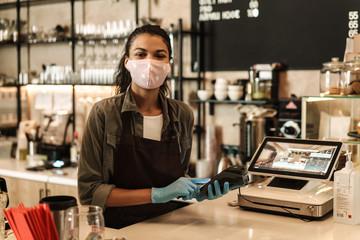 Woman barista wearing medical face mask