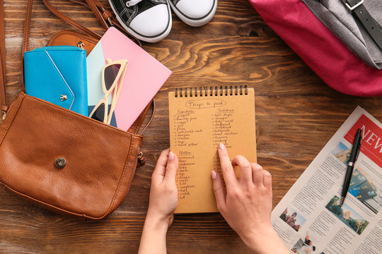 Woman making check-list of things to pack for travel