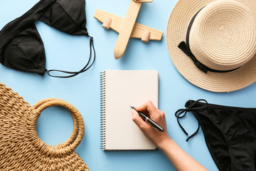 Fototapeta Woman making check-list of things to pack for travel