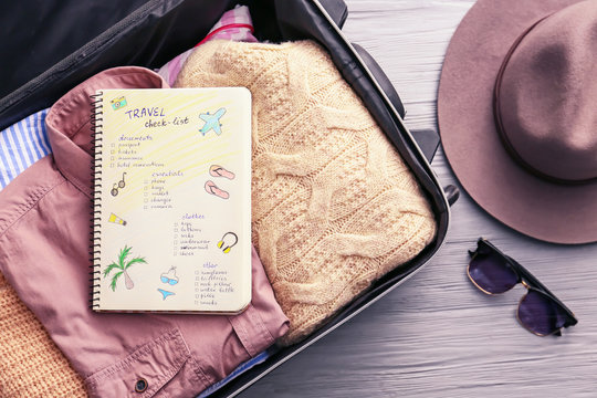 Notebook with check-list for travel and packed things in suitcase