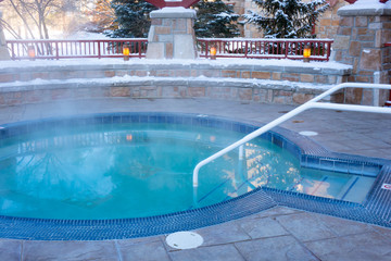 Steaming public outdoor hot tub with surrounding stone and tile block with no people in winter season in Michigan, USA.