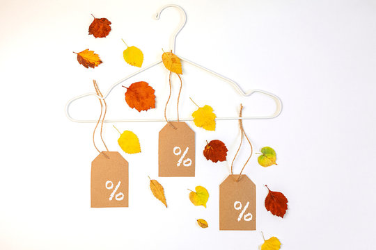 Autumn creative composition, top view, flat layer, clothes hangers, dried bright colored leaves on a white background, copy space, sales template, layout, flyers. Top view, copy space