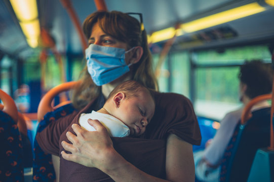 Mother with baby in sling wearing face massk on the bus