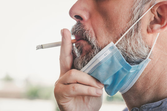 covid-19,Close-up of man with medical mask smoking a cigarette at the street