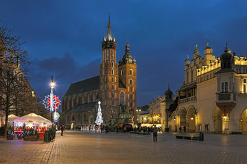 Krakow, Poland. Evening view of Main Square (Rynek Glowny) with St. Mary's Basilica in brick Gothic style, Cloth Hall in Renaissance style, and Christmas market between them.