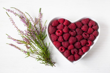Raspberry berries in a heart shape bowl and heather flowers