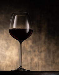 Elegant stemmed glass goblet filled with red wine placed on table against blurred shabby background