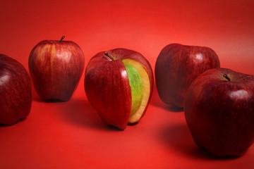 entre varias manzanas rojas una es verde por dentro, sobre fondo rojo