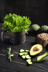 Fresh green vegetables and loaf of rye bread placed on wooden rustic table