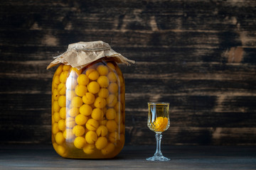 Homemade tincture of yellow cherry plum in glass jar and a wine crystal glass on wooden background, Ukraine, close up