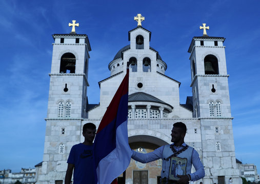 A supporter of pro-Serbian parties holds a Serbian flag and an icon in front of Serbian Orthodox Cathedral of the Resurrection of Christ, ahead of Montenegrin Assembly election in Podgorica