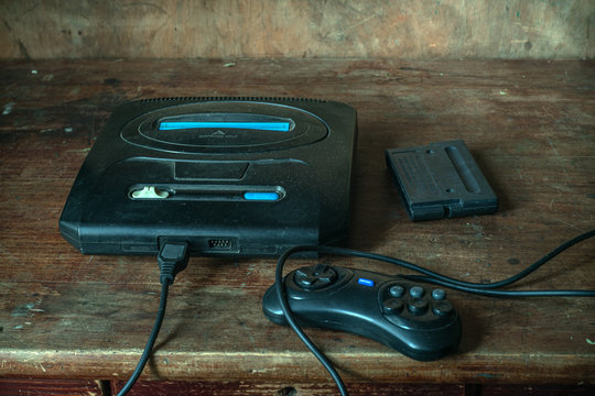 An old game console with a cartridge and a joystick from the 90s, in the dust on a wooden table in the dust