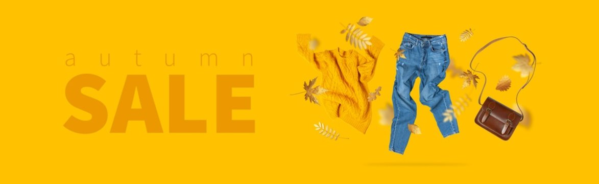Autumn sale. Fall shopping. Yellow flying women's knitted sweater, blue jeans, leather bag, golden autumn leaves on yellow background. Creative clothing concept, discounts in stores. Flat lay fashion