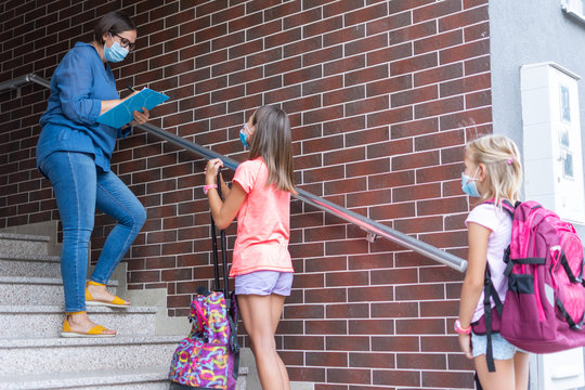 Teacher with face mask welcoming children back at school after lockdown. I miss school.
